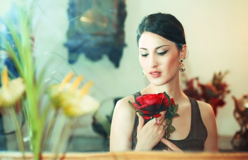 A woman admiring a rose