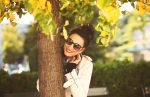 A woman wearing sunglasses smiling behind a tree